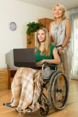 Woman and handicapped girl with laptop — Stock Photo