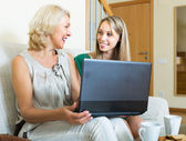 Woman learnig to use laptop from girl — Stock Photo