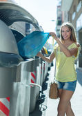 Girl with rubbish near refuse  container — Stock Photo