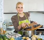 Smiling woman cutting white fish — Stock Photo