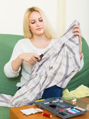 Housewife stitching tears of clothes — Stockfoto