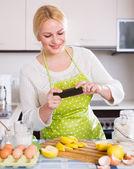 Menina com smartphone na cozinha — Fotografia Stock