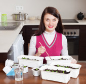 Brunette girl working with  seedlings at table  — Stock Photo