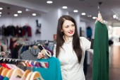 Happy female buyer with sweaters — Stock Photo