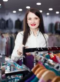 Smiling female buyer choosing clothes — Stock Photo