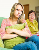 Worried mother  beside her resentful daughter — Stock Photo