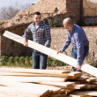Workmen arranging building timber at farm   — Stockfoto #69431637