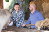 Two farmers with pitchforks — Stock Photo