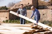 Workmen arranging building timber at farm — Stock Photo