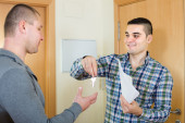 Two men at doorway with keys — Stock Photo