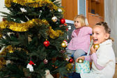 Happy children decorating christmas tree — Stock Photo