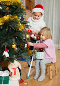 Little girls decorating Christmas tree — Stock Photo