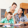 Couple with teenager son doing homework — Stock Photo #69442995