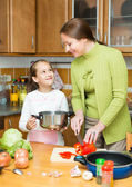Mother with daughter cooking at kitchen — Stock Photo