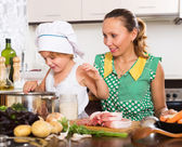 Woman with baby cooking at kitchen — Stock Photo