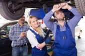 Mechanic and assistant working at auto repair shop — Stock Photo
