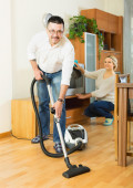 Spouses dusting and hoovering — Stock Photo