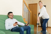 Wife hoovering room, husband relaxing  — Stock Photo