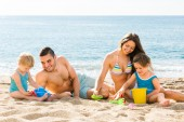 Parents helping toddlers to dig sand — Stock Photo