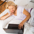 Mature woman with laptop in bed — Stock Photo #72147437
