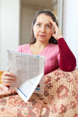 affliction mature woman with newspaper   — Stock Photo