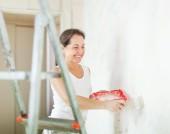 Happy mature woman paints wall — Stock Photo