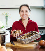 Happy mature woman with dried mushrooms — Stock Photo