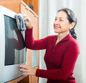 Smiling mature woman dusting TV   — Stock Photo