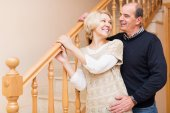 Smiling spouses leaning against stairway — Stock Photo