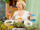 Mulher madura com ervas na mesa — Fotografia Stock