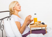 female pensioner having  breakfast in bed — Stock Photo