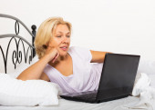 Girl with laptop laying — Stock Photo