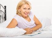 Ώριμη γυναίκα, γράφοντας στο ημερολόγιο — Φωτογραφία Αρχείου
