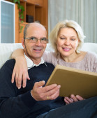 Senior spouses with picture album — Stock Photo