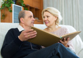 Pensioners watching old photoes — Stock Photo