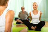 Yoga instructor with elderly attenders — Stock Photo