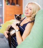 Woman playing with Siamese kitten — Fotografia Stock