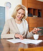 Mature woman with  documents and tea   — Stock Photo