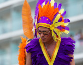 Performer in colored feathers at Gay pride   — Stock Photo