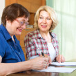 Two  women  signing documents at home — Foto Stock #72168855