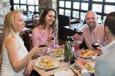 Young people enjoying food at tavern — Stock Photo
