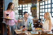 Adults having dinner and waiter — Stock Photo