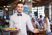 Happy waiter with a tray — Stock Photo