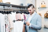Man choosing new female garment — Foto de Stock