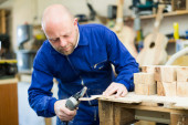 Man working on a machine at wood workshop — Stock Photo