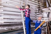 Workers searching for profiles on rack — Stock Photo