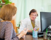 Mature doctor with patient — Stock Photo