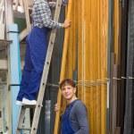 Two workers choosing PVC window profile — Stock Photo #72175923