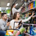Shoppers choosing bottle of wine — Stock Photo #72177385