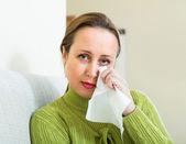 Smutna kobieta na kanapie w domu — Zdjęcie stockowe